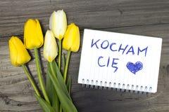 Tulpenboeket en blocnote met woorden ` kocham ciÄ™ ` Stock Foto's