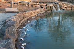 Tulsa, l'Oklahoma - 17 février 2018 Les ordures et les débris honteux polluent un étang d'eau en parc de ville Images libres de droits