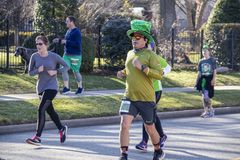 Tulsa USA 3 - 16 - 2019 Man in sequined green top hat surrounded by other people jogging down urban residential street in annual. Saint Patrick`s Day run royalty free stock photos
