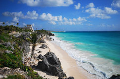 Tulum Beach, Mexico. A view along the cliffs and beach at Tulum Beach, Mexico, with Mayian ruins visible on the cliffs overlooking the water stock image