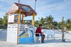 Tulum fishing adventures. TULUM, MEXICO - JANUARY 23, 2015: A local fisherman sits at a kiosk on a white sand beach offering fishing tours to catch local Royalty Free Stock Photography