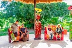 TULUM MEXICO - JANUARI 10, 2018: Oidentifierat folk som sitter på det fria i färgrika stolar bredvid en kvinnaskalle Royaltyfri Foto
