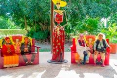 TULUM MEXICO - JANUARI 10, 2018: Oidentifierat folk som sitter på det fria i färgrika stolar bredvid en kvinnaskalle Arkivfoto