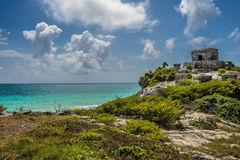 Tulum Pyramid. Ruins next to light blue waters Royalty Free Stock Photography