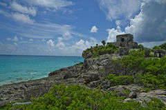 The Tulum temple sits high on a rocky cliff overlooking the turquoise water along the coast of Quintana Roo. Stock Photo