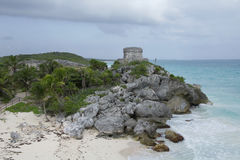 Tulum Winds God Temple and Cliffs. Photo of the Temple of the Winds God at Mayan ruin site in Tulum Mexico also showing surrounding rocky coastline in foreground royalty free stock photo