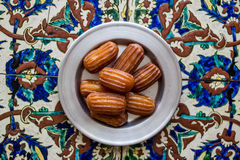 Tulumba Tatlisi / Turkish Traditional Dessert on a Ottoman Pattern. Stock Photo
