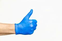 tum upp Profilera sikten av handen i blå medicinsk handske royaltyfri bild