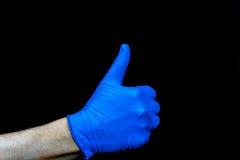 tum upp Profilera sikten av handen i blå medicinsk handske royaltyfri foto