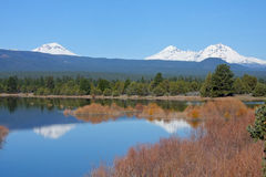 Tumalo Reservoir in May. The Three Sisters reflect in the water at Tumalo Reservoir 9 miles northwest of Bend, Oregon.  Usually dry most of the year, the shallow Stock Photography