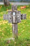 Tumba cristiana con la cruz y el entierro de piedra en un prado verde Fotos de archivo