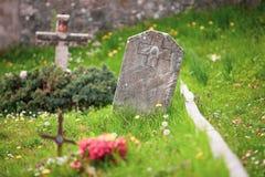 Tumba cristiana con la cruz y el entierro de piedra en un prado verde Foto de archivo