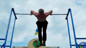 Tumble on the bar, pull-ups, strength training outdoors. Kherson, Ukraine - 01 june 2016: Tumble on the bar, pull-ups, strength training outdoors in Kherson 01 stock video footage