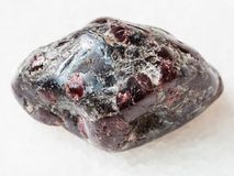 Tumbled Almandine garnet crystals on white marble. Macro shooting of natural mineral rock specimen - tumbled Almandine garnet and biotite crystals in gemstone on stock photography