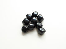 Tumbled Black Obsidian stones close up on table for crystal ther Stock Images