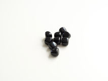Tumbled Black Obsidian stones for crystal therapy treatments and Stock Photos