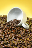 Tumbled coffee cup over roasted beans Stock Image