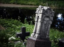 A tumbled-down monument to the cemetery with a cross on the back royalty free stock photos