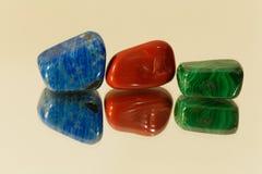 Tumbled gemstones on a mirror Stock Photos