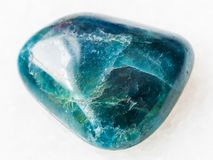 Tumbled green blue Apatite gemstone on white. Macro shooting of natural mineral rock specimen - tumbled green blue Apatite gemstone on white marble background stock image