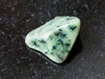 Tumbled green Grossular gemstone on dark Royalty Free Stock Images