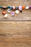 Tumbled healing crystals border on wooden background Royalty Free Stock Image