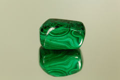 Tumbled malachite on a mirror. A piece of tumbled malachite on a mirror royalty free stock images