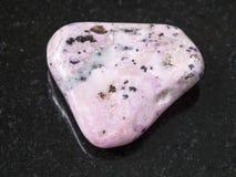 Tumbled rhodochrosite gem on dark background. Macro shooting of natural mineral rock specimen - tumbled rhodochrosite gem on dark granite background from Peru Stock Photo