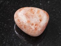 Tumbled sunstone (heliolite) gem stone on dark Stock Photos