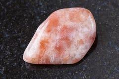 Tumbled sunstone (heliolite) gemstone on dark Royalty Free Stock Photography