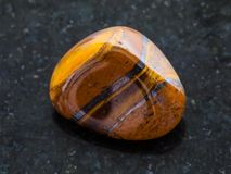 Tumbled tigers eye gemstone on dark background. Macro shooting of natural mineral rock specimen - tumbled tigers eye gemstone on dark granite background Royalty Free Stock Photography