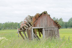 Tumbledown barn on a field. That will fall apart any minute Stock Photography