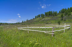 Tumbledown corral in a meadow. The foothills of the Sayan Mountains, Eastern Siberia, Russia Stock Images