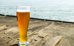 A tumbler of beer. A glass of beer, standing on a wooden table on the quay of ferries on the Elbe Royalty Free Stock Photo