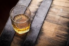 Whiskey on a barrel. Tumbler glass of whiskey standing on a barrel in a cellar stock photography