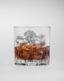 Tumbler of glowing golden brandy and ice Stock Photography