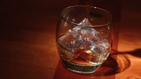 Tumbler of ice being filled with whiskey. On wooden surface stock video