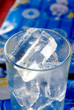 Tumbler and ices. Focus on top ice Royalty Free Stock Photo