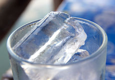Tumbler and ices. Focus on top ice Stock Images