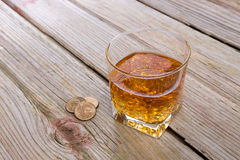 Tumbler of whiskey and tip on a bar counter Royalty Free Stock Images