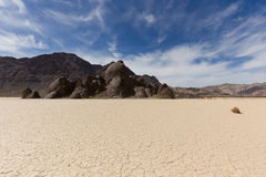 Tumbleweed on dry lake floor with cracked mud. Mountains and sky with clouds. Racetrack Playa. Death Valley national park. California Royalty Free Stock Image
