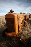 Tumbleweeds piled against abandoned tractor Royalty Free Stock Photography