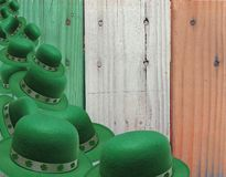 Tumbling Green Leprechaun Hats Over Irish Flag Colored Boards. This an image of many green Leprechaun hats tumbling over each other in front of a background of stock photography