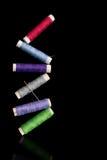 Tumbling reels of cotton thread. Stock Photo