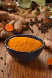 Tumeric in a bowl on wooden background. Stock Images