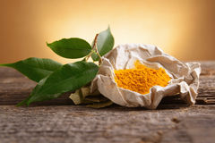 Tumeric powwder spice. On wooden board with fresh leaves Royalty Free Stock Photos