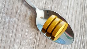 Tumeric tablets on a teaspoon. Tumeric tablets being measured onto a teaspoon for a cancer patient Royalty Free Stock Image