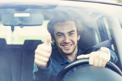 Tummar för ung man gör en gest upp i bil Arkivbild