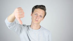 Tummar ner, fel, ogillar, den isolerade gesten av den unga mannen Royaltyfri Foto