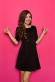 Tummar upp för svart klänning Arkivfoton